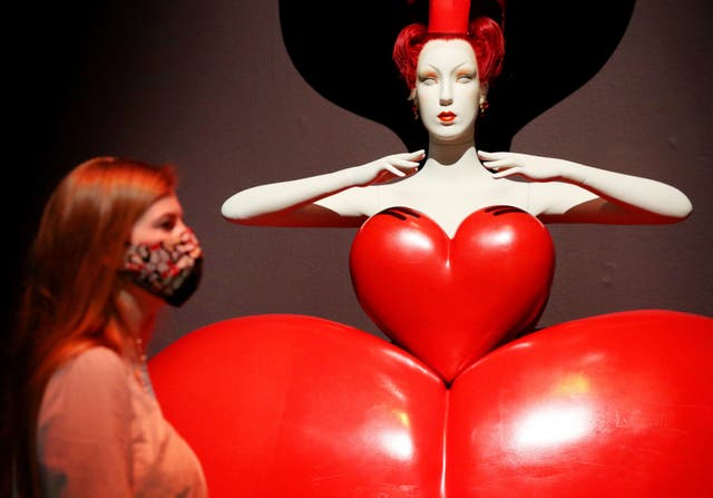An employee stands before a costume for the Queen of Hearts by Bob Crowley on display at the Alice: Curiouser and Curiouser exhibition at the Victoria and Albert Museum in London