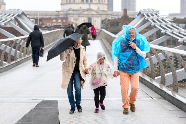 A family buffeted by the wind whilst crossing the the Millennium Bridge in London, with wind and rain forecast to ravage the UK on the first Friday that people have been allowed to meet in large groups outside in England