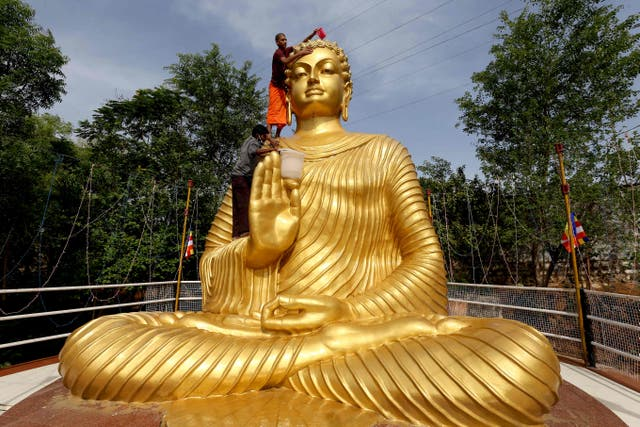 A Buddhist monk climbs atop a giant statue of Buddha, to wash and decorate on the eve of Buddha Purnima, a holiday traditionally celebrated for Buddha's birthday also known as Vesak celebrations, in Bhopal