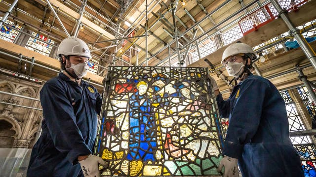 York Glaziers Trust employees Kieran Muir (la gauche) and Emily Price (droite) remove a stained glass window panel at the start of a new five year, £5m project to conserve York Minster's South East Transept and its medieval St Cuthbert Window