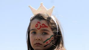 A girl, with her face painted with the colours of the opposition flag, looks on during a demonstration against Syria's President Bashar al-Assad and presidential elections, in the opposition-held Idlib, Syria