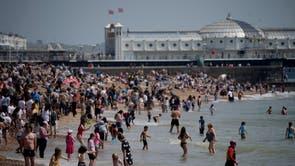 Mense durf die see in terwyl hulle hulself geniet tydens 'n warm dag op Brighton Beach