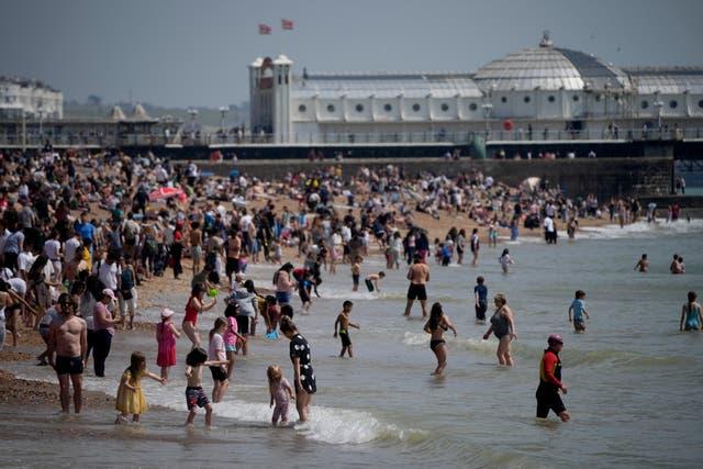 ブライトンビーチで暑い日を楽しんでいる人々は、海に足を踏み入れます