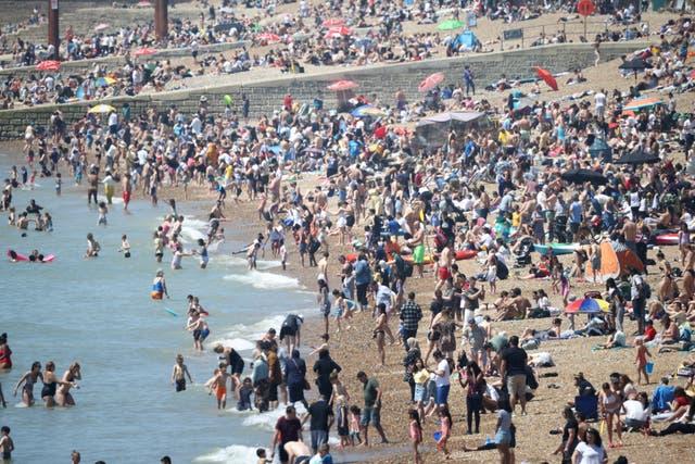 人々はブライトンビーチで暑い天気を楽しんでいます