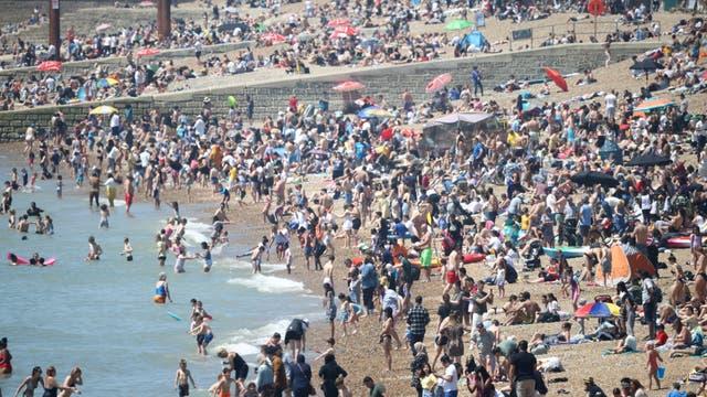 Mense geniet die warm weer op Brighton-strand
