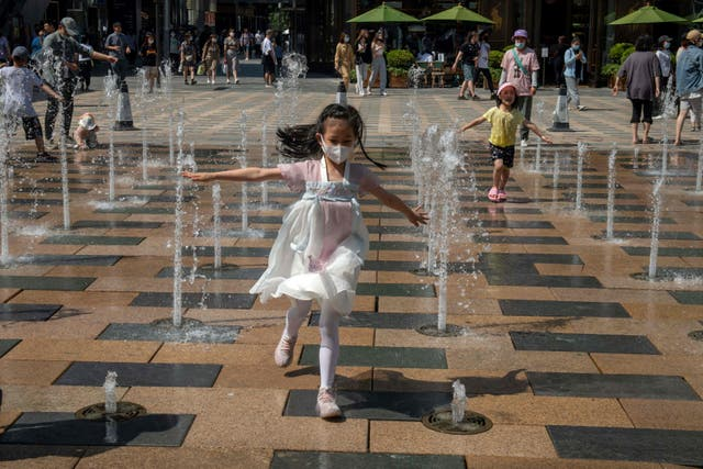 A girl runs through a fountain outside a shopping mall on International Children's Day in Beijing on June 1, 2021, a day after China announced it would allow couples to have three children.