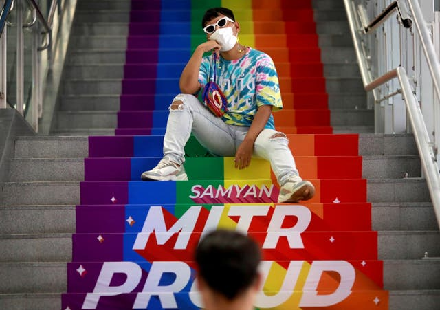 A couple take photos of each other on a rainbow flag-themed path during pride month at Samyan MRT station in Bangkok, Thailand