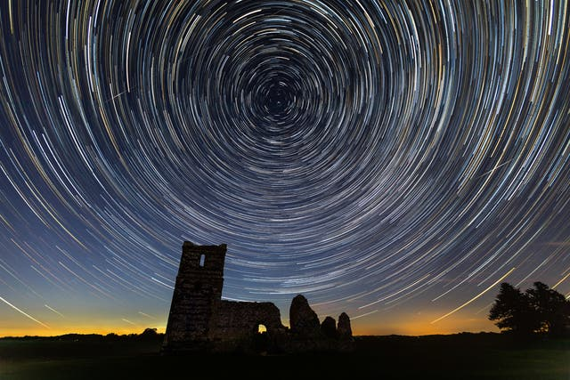 Et fotografi med lang eksponering fanger jordens rotasjon når stjernene sløres ut i sirkler over Knowlton kirkeruiner i Dorset