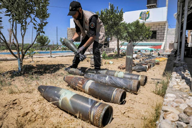 An explosives expert from Hamas lays out unexploded projectiles from the aftermath of the May 2021 conflict with Israel, at a local police precinct in Khan Yunis in the southern Gaza Strip
