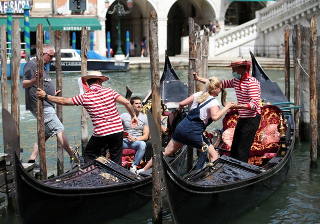 """Gondoliers help tourists to get on the gondolas, as the region of Veneto becomes a """"white zone"""", following a relaxation of Covid-19 restrictions with only masks and social distancing required, in Venice, Italia"""
