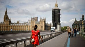 En fotgjenger med ansiktsdekning går over Westminster Bridge nær Houses of Parliament i sentrum av London