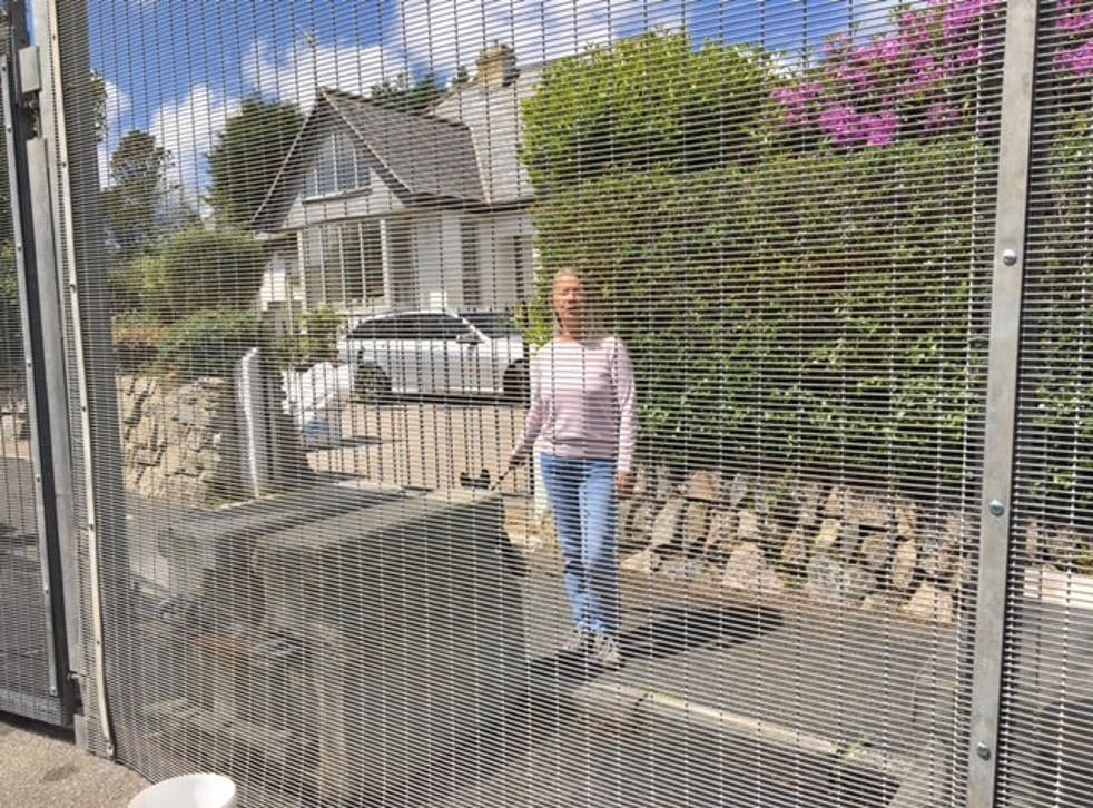 <p>Christine Norton behind security fencing installed across Crabis Bay and St Ives</p>