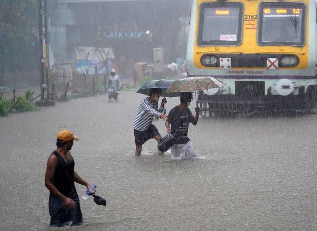 People cross waterlogged railway tracks next to a parked passenger train during heavy rains in Mumbai, India