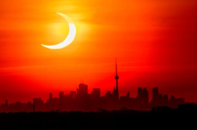 An annular solar eclipse rises over the skyline of Toronto