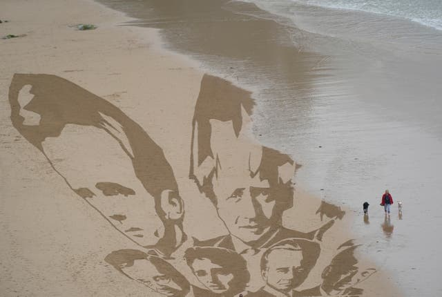En kvinne går med hundene sine når det innkommende tidevannet begynner å vaske bort hodene til G7-ledere trukket i sanden av aktivister på stranden ved Newquay, Cornwall