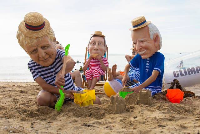 Oxfam campaigners wearing costumes depicting G7 leaders pose for photographers on Swanpool Beach near Falmouth, Cornwall