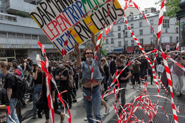 Tape is lifted by air leaving a vent from the metro system as thousands of activists take part in the anti-extreme right 'March of Freedoms' in Paris, Frankrike
