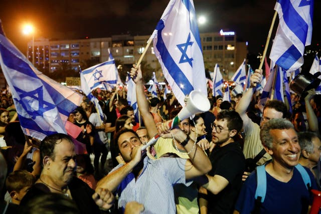 eople celebrate after Israel's parliament voted in a new coalition government, ending Benjamin Netanyahu's 12-year hold on power, at Rabin Square in Tel Aviv, Israel