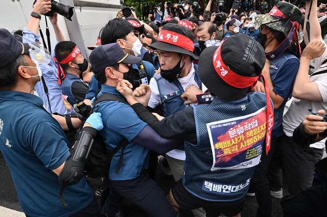 Parcel delivery workers scuffle with police officers as they try to bring loudspeakers, an unauthorised protest item, during a rally calling for improvement of working conditions in Seoul