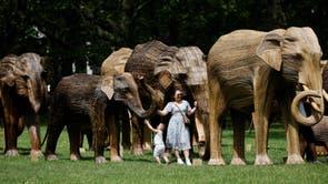 女性と子供が、象の家族とリアルエレファントコレクティブによって設立されたアジアゾウの群れの等身大の彫刻を調べて、象と人間が惑星の生物多様性をよりよく保護する方法について一般の人々を教育するのを支援します, グリーンパークで, ロンドン中心部