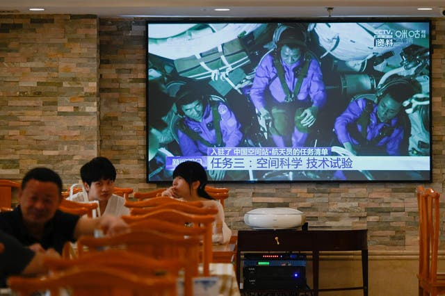 A TV broadcasts Chinese astronauts in Shenzhou spacecraft, at a restaurant in Beijing