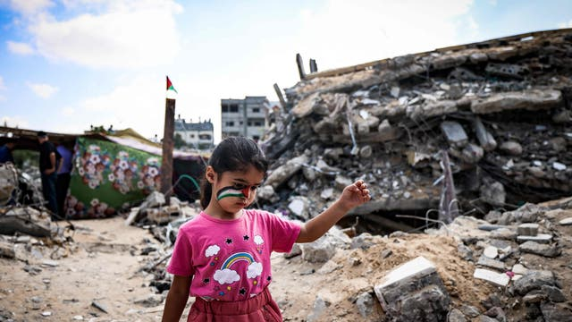 A Palestinian girl with a national flag painted on her face, plays amidst the rubble of buildings destroyed by last month's Israeli bombardment of the Gaza Strip, in Beit Lahia