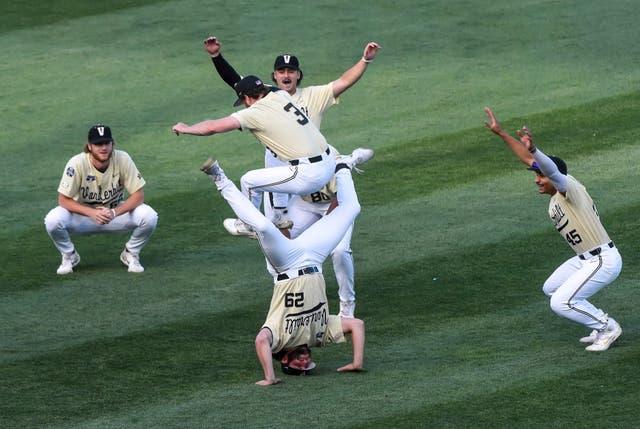 Jun 21, 2021; Omaha, Nebraska, USA;  Vanderbilt Commodores outfielder Cooper Davis (3) leaps over pitcher Nick Maldonado (29) in between inning action against the NC State Wolfpack at TD Ameritrade Park