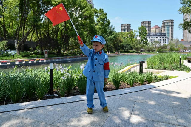 A child holds a Chinese flag near the museum of the First National Congress of the Chinese Communist Party during a media tour organised by the local government in Shanghai on June 22, 2021
