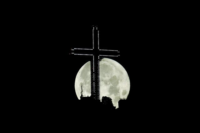 The last super moon of 2021 behind the 66-metre tall Millennium cross in Skopje, Nord -Makedonia