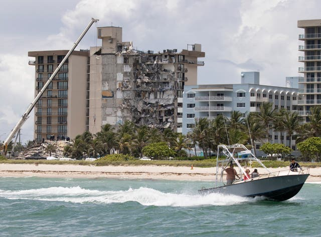 A boat passes off shore as members of the South Florida Urban Search and Rescue team look for possible survivors in the partially collapsed 12-story Champlain Towers South condo building