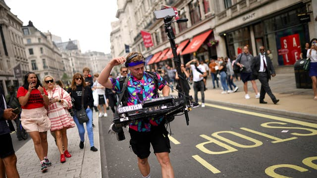 People walk along Regent Street in central London during a #FreedomToDance march organised by Save Our Scene, in protest against the government's perceived disregard for the live music industry throughout the coronavirus pandemic
