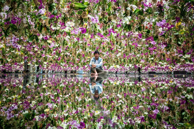 """Toshiyuki Inoko, leader of TeamLab, poses for a photo following an interview with AFP in an interactive kinetic installation """"Floating Flower Garden: Flowers and I are of the Same Root, the Garden and I are One"""" during a media preview of the TeamLab Planets Garden Area in the Toyosu district of Tokyo"""