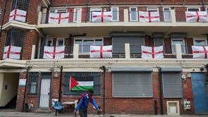 ロンドンのカービー住宅団地で、主にイギリスの旗で飾られたバルコニーと踊り場の前で少年がサッカーボールを蹴る