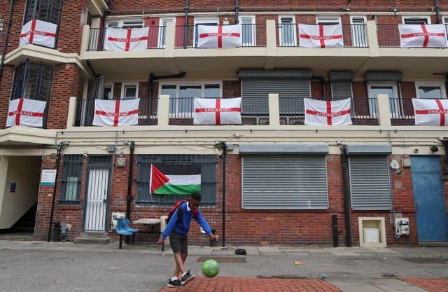 Un garçon frappe un ballon de football devant les balcons et les paliers ornés de drapeaux principalement anglais dans le lotissement Kirby à Londres