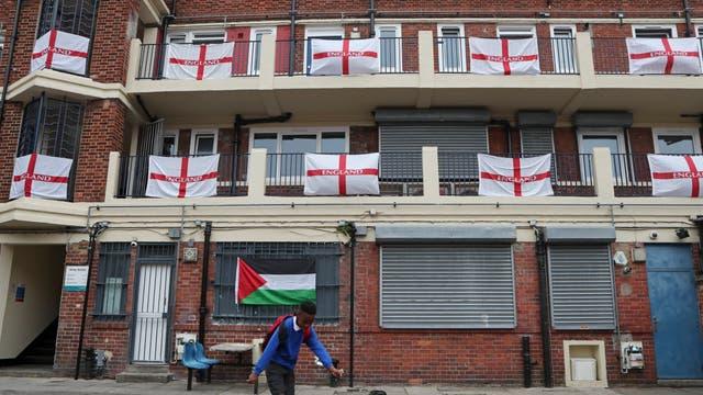Um menino chuta uma bola de futebol em frente às varandas e patamares adornados predominantemente com bandeiras da Inglaterra no bairro residencial Kirby, em Londres
