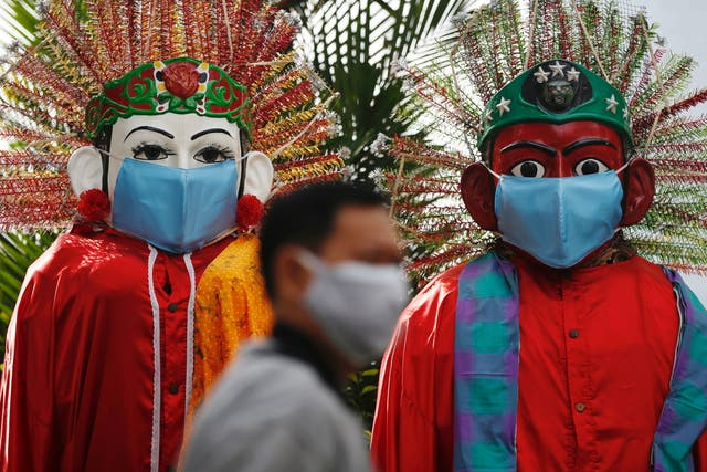 """A man walks past traditional large figures called """"Ondel-ondel"""", donning face masks and displayed along a sidewalk of a main road, in Jakarta, Indonesia"""