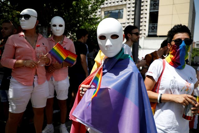 Members and supporters of LGBT community wear masks and hold rainbow flags as they gather during the annual gay pride parade in Pristina, Kosovo