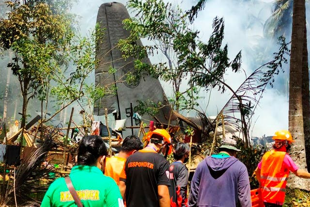 In this photo released by authorities, rescuers search for bodies from the site where a Philippine military C-130 plane crashed in Patikul town, Sulu province, Filippinene