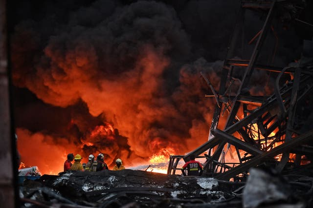Firefighters work at the site of an explosion and fire at a plastics factory on the outskirts of Bangkok