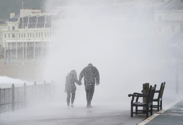 Un couple est touché par une vague alors qu'ils marchent le long de la promenade de Douvres, Kent, lors de vents forts