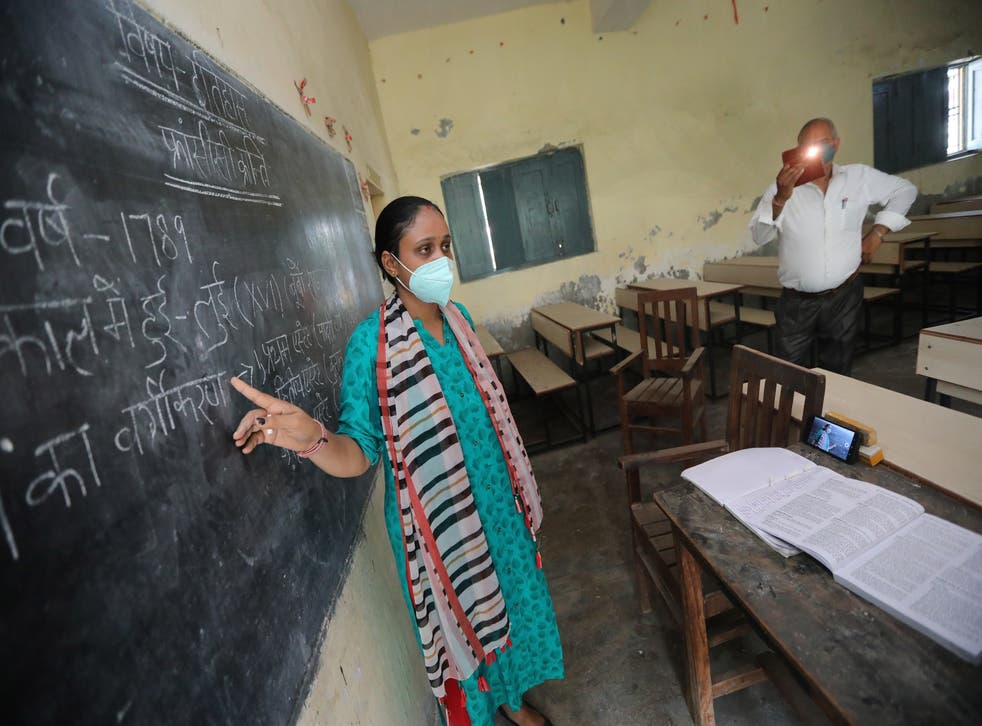 <p>FILE. Indian school teacher at Gandhi Smarak school in Raghunathpur records a history lesson via mobile phone for students at the school on the outskirts of New Delhi</磷>
