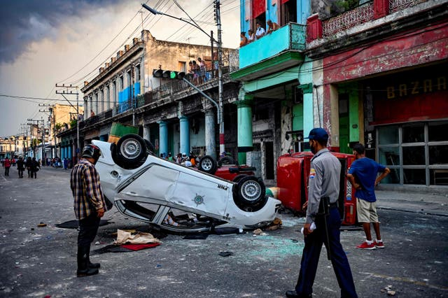 Police cars are seen overturned in the street in the framework of a demonstration against Cuban President Miguel Diaz-Canel in Havana