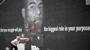 A local resident puts love hearts and slogans on the plastic that covers offensive graffiti on the vandalised mural of Manchester United striker and England player Marcus Rashford on the wall of a cafe on Copson Street, Withington in Manchester