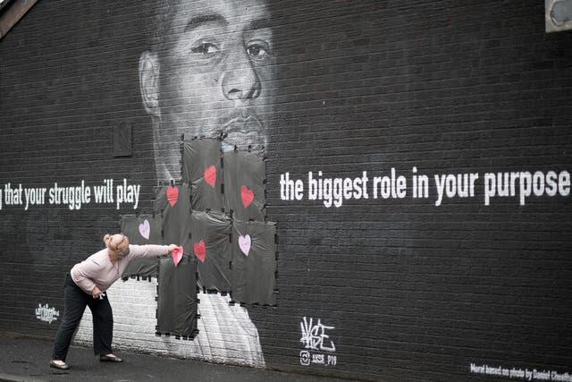 Un résident local met des cœurs d'amour et des slogans sur le plastique qui recouvre des graffitis offensants sur la peinture murale vandalisée de l'attaquant de Manchester United et joueur anglais Marcus Rashford sur le mur d'un café de Copson Street, Withington à Manchester