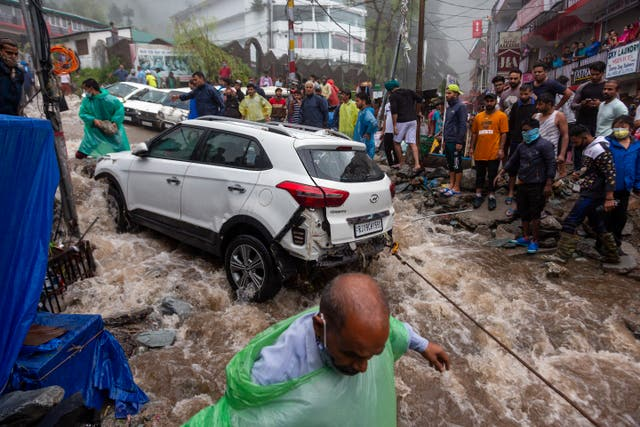 People try to recover a car damaged during flash floods after heavy monsoon rains in Bhagsunag, a popular tourist town in Himachal Pradesh, India