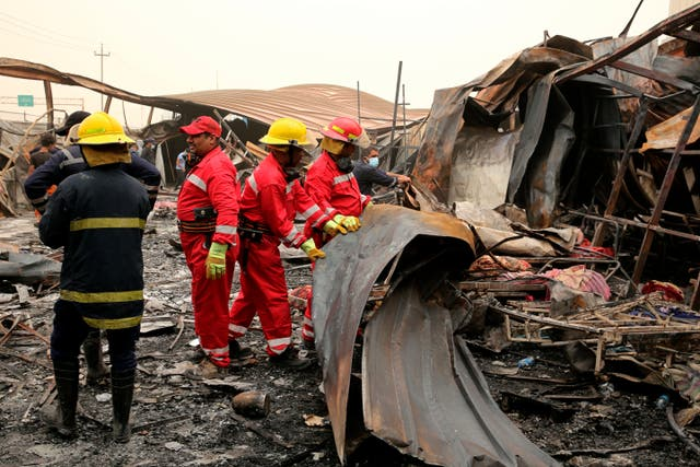 Rescuers look for bodies after a catastrophic blaze erupted Monday at a coronavirus hospital ward in the al-Hussein Teaching Hospital, in Nasiriyah, Iraq