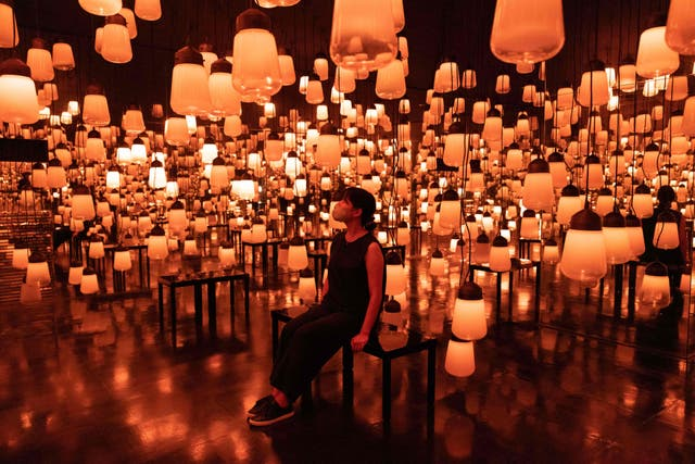 """A staff member sits at an interactive digital installation """"Fire / Forest and Spiral of Resonating Lamps in the Forest"""" during a media preview of """"teamLab: A Forest Where Gods Live"""" at the lobby of Mifuneyama Rakuen Hotel, Takeo Hot Springs in Saga prefecture"""
