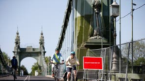 Cyclists ride over the Hammersmith Bridge in London. The bridge was closed last year after cracks in it worsened during a heatwave