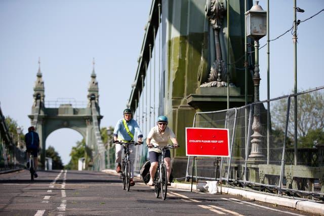 Les cyclistes roulent sur le pont Hammersmith à Londres. Le pont a été fermé l'année dernière après que des fissures se soient aggravées lors d'une vague de chaleur