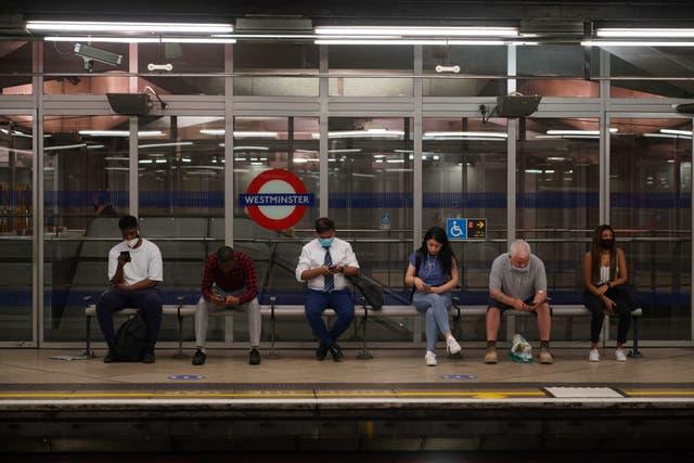 Les navetteurs, certains ne portent pas de masques,  à la station de métro Westminster, à 08:38 à Londres après la levée des dernières restrictions légales sur les coronavirus en Angleterre